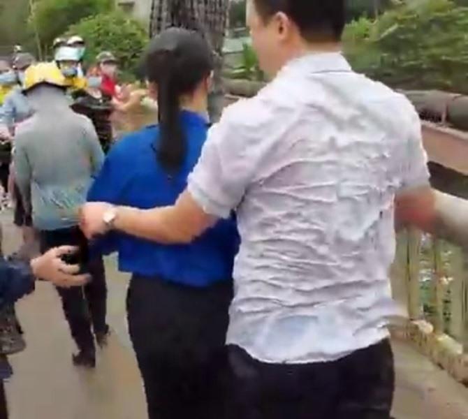 Anh Sinh (người mặc áo trắng) tại thời điểm nhảy xuống sông cứu cô gái trẻ lên bờ. Ảnh: Cắt từ Clip