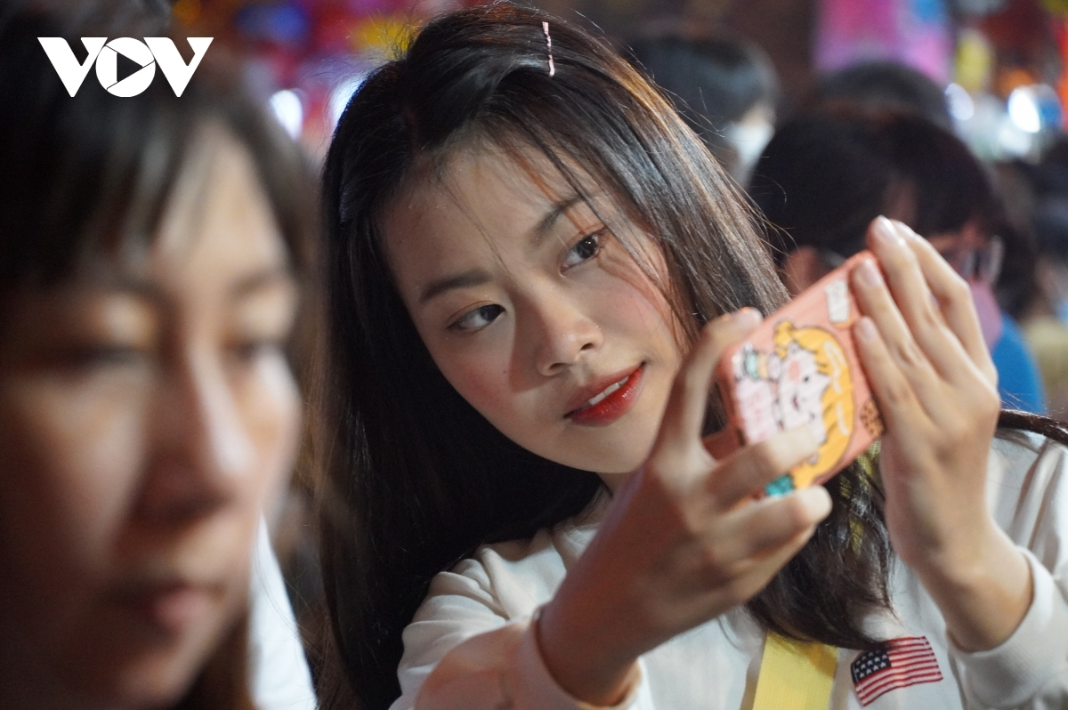 Young people enjoy taking selfies during the Full-Moon Festival celebrations.