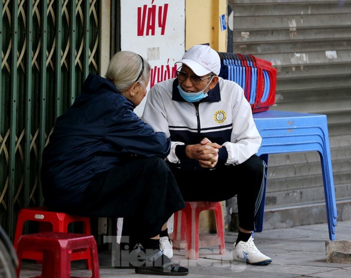 An elderly couple happily sit together as they stay warm in the winter.