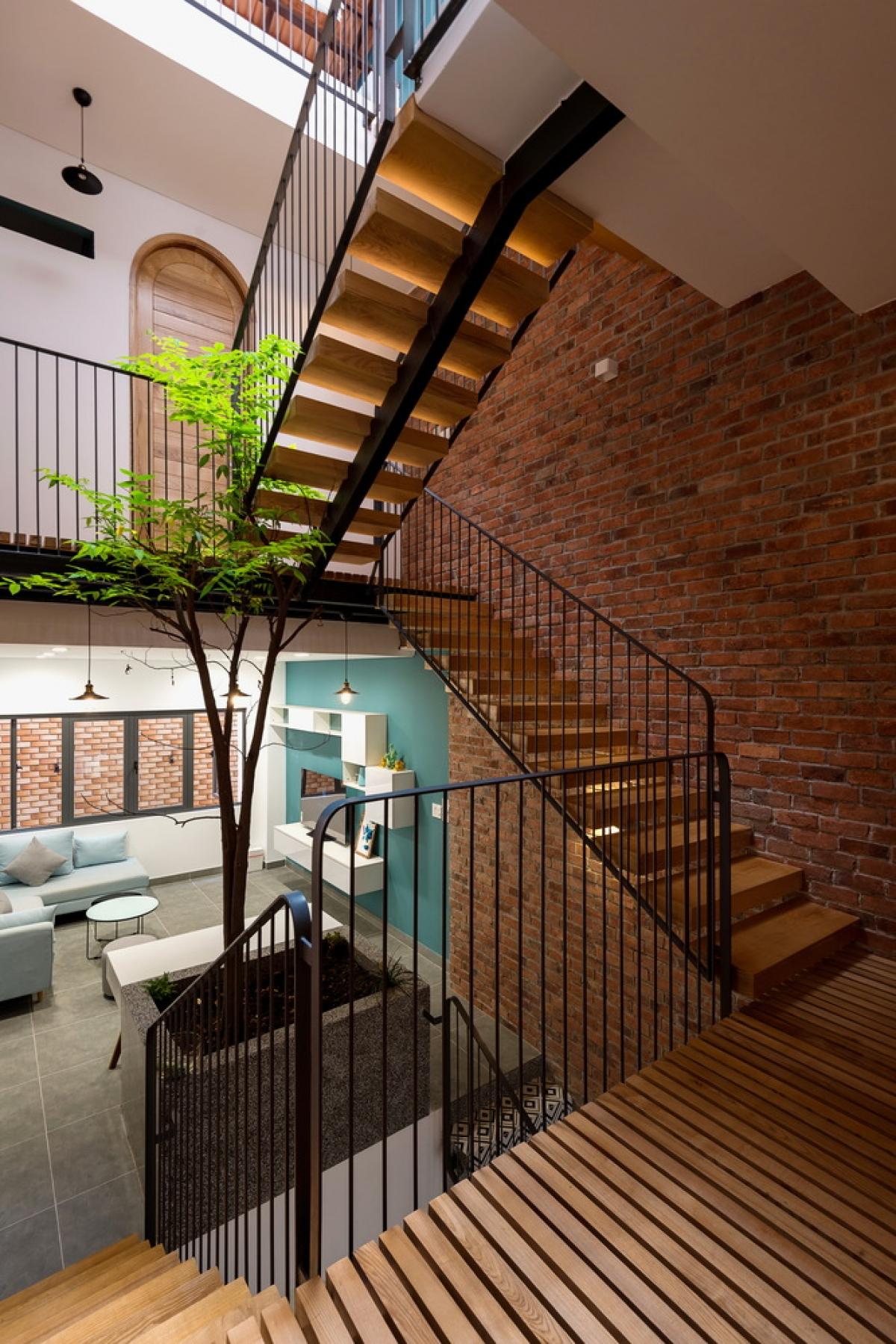 Cầu thang gỗ có tay vịn bằng thép, kết nối các tầng trong căn nhà.