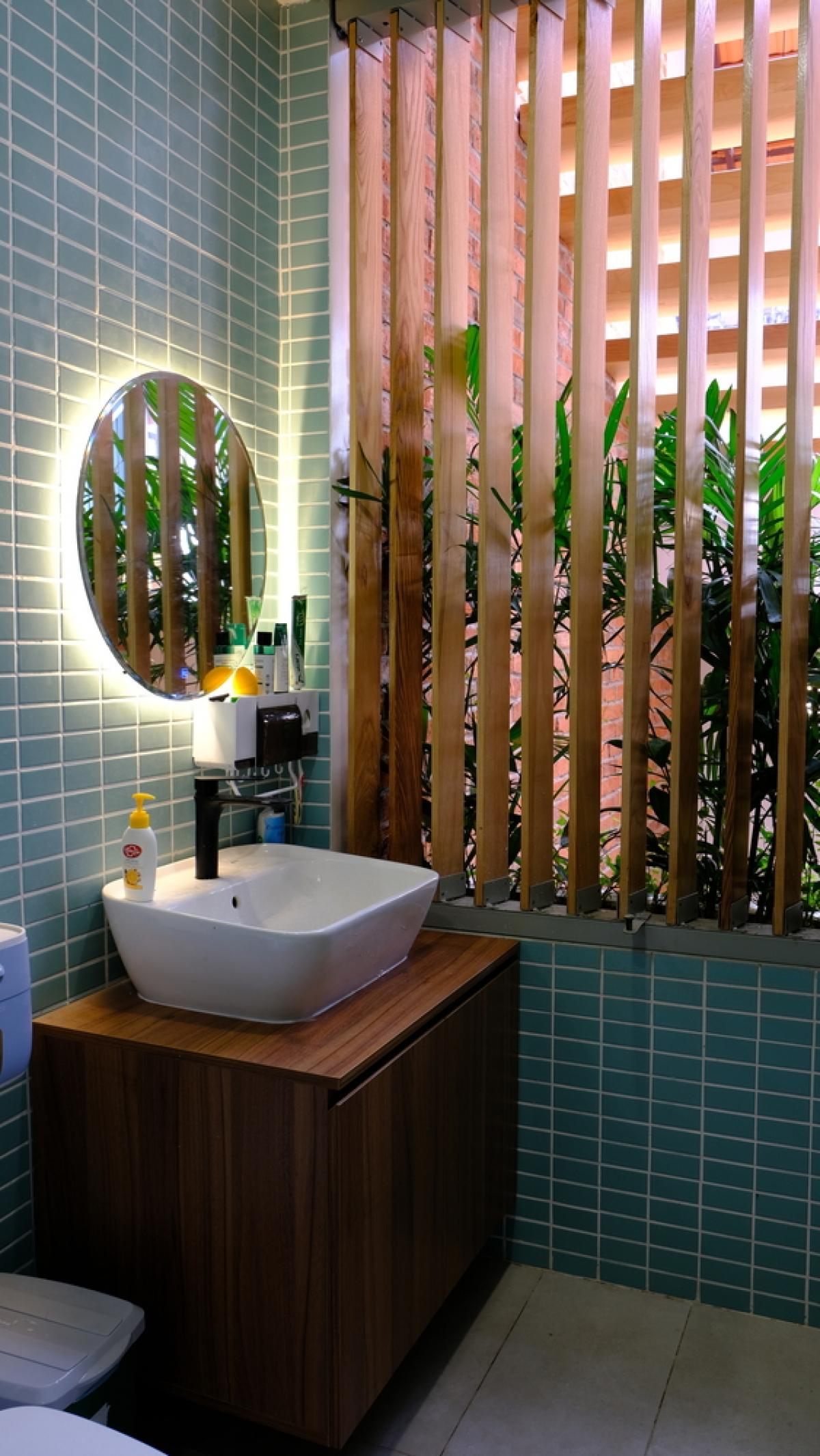 Bồn rửa tay tầng trệt sử dụng đá ốp màu xanh mang đến cảm giác mát mẻ.