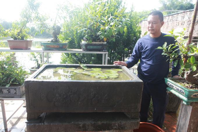Mặt trước khắc hình chiếc khánh, bên trong có hình trái đào và hoa, ba mặt còn lại để trơn. Theo anh Tuấn, bể này các cụ xưa thường để đựng nước mưa.