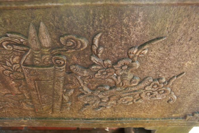 Một bên cuốn thư là hình ảnh con rồng thời Lý, phía trênrồng có những cành mai