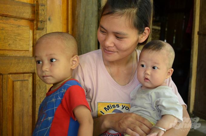 Người mẹ trẻ bên con, cháu. Ảnh: Dương Đình Tường.