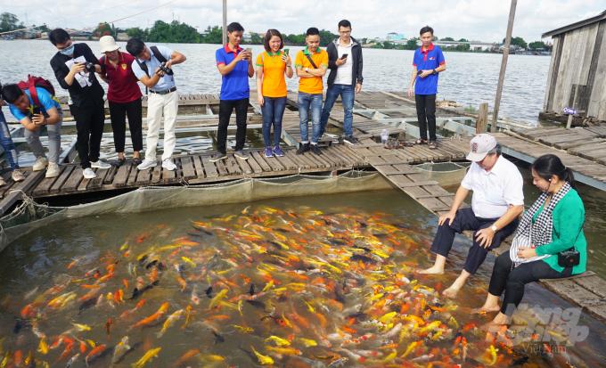 Khách tham quan làng bè nuôi cá ở Cồn Sơn. Ảnh: Ngọc Bích.