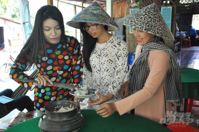 Thôn nữ Cồn Sơn nấu cơm bằng nồi đồng xưa đãi khách. Ảnh: Hữu Đức.