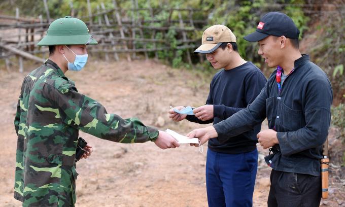 Chiến sĩ Đồn Si Pa Phìn phát khẩu trang cho người dân trong lúc tuần tra. Ảnh: Bảo Thắng.