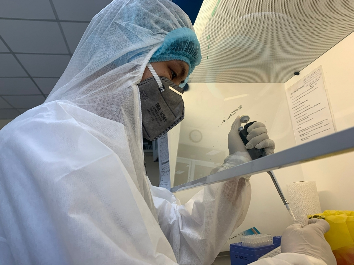 A healthcare worker examines COVID-19 testing results in the lab.