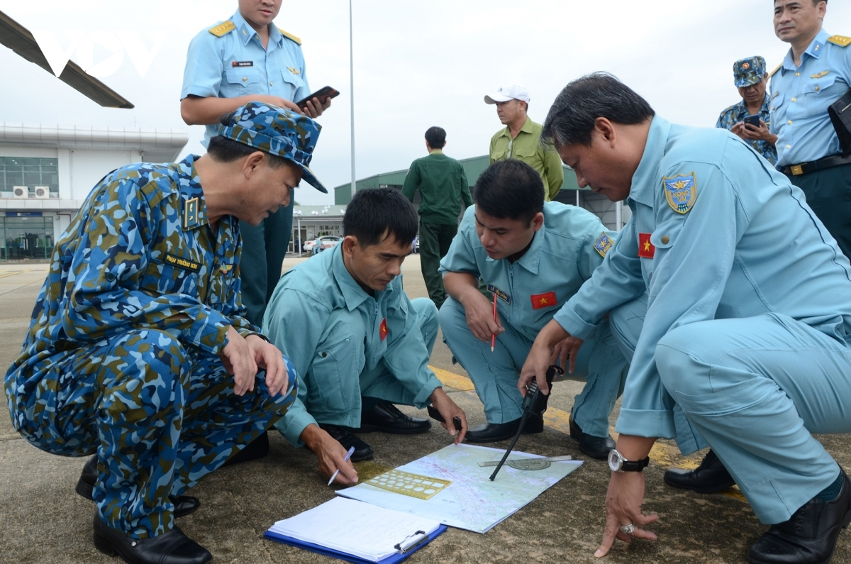 A military helicopter takes off from Phu Bai airport and heads over to the landslide area at Rao Trang 3 Hydropower Plant to take part in search and rescue efforts. Pictured is Colonel Vu Hong Son, Head of Air Force Division 372 (first from right), as he checks the flight path and crew members