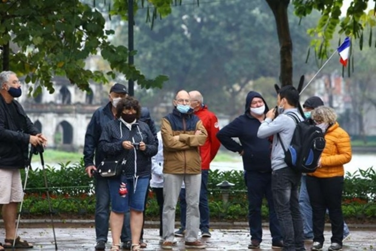 Foreign travellers are seen wearing face masks walking along Hoan Kiem Lake in Hanoi capital when the epidemic broke out in Vietnam. (Photo: VNA).