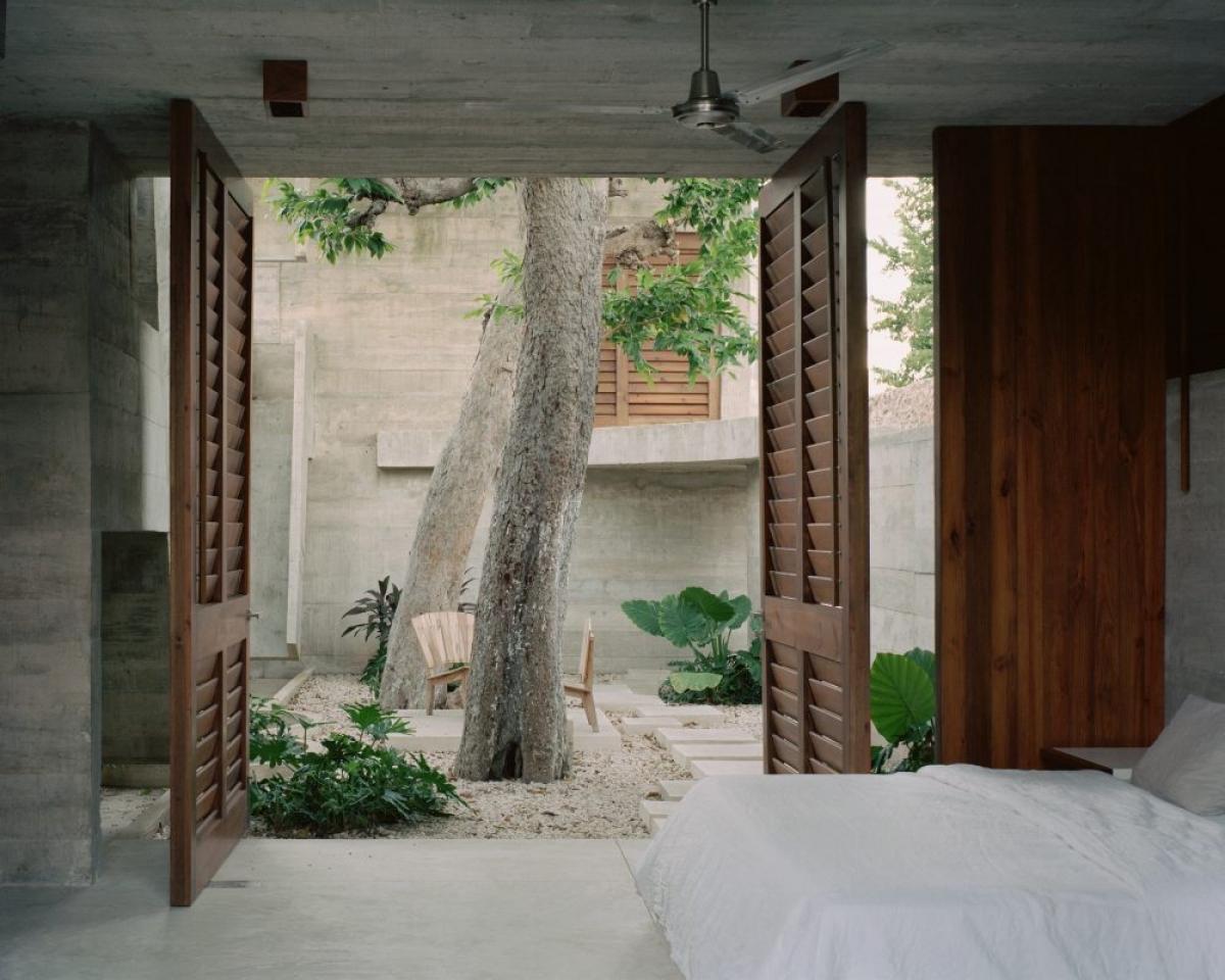 Phòng ngủ nhẹ nhàng với màu trắng, có cửa lớn đi ra vườn cây xanh.