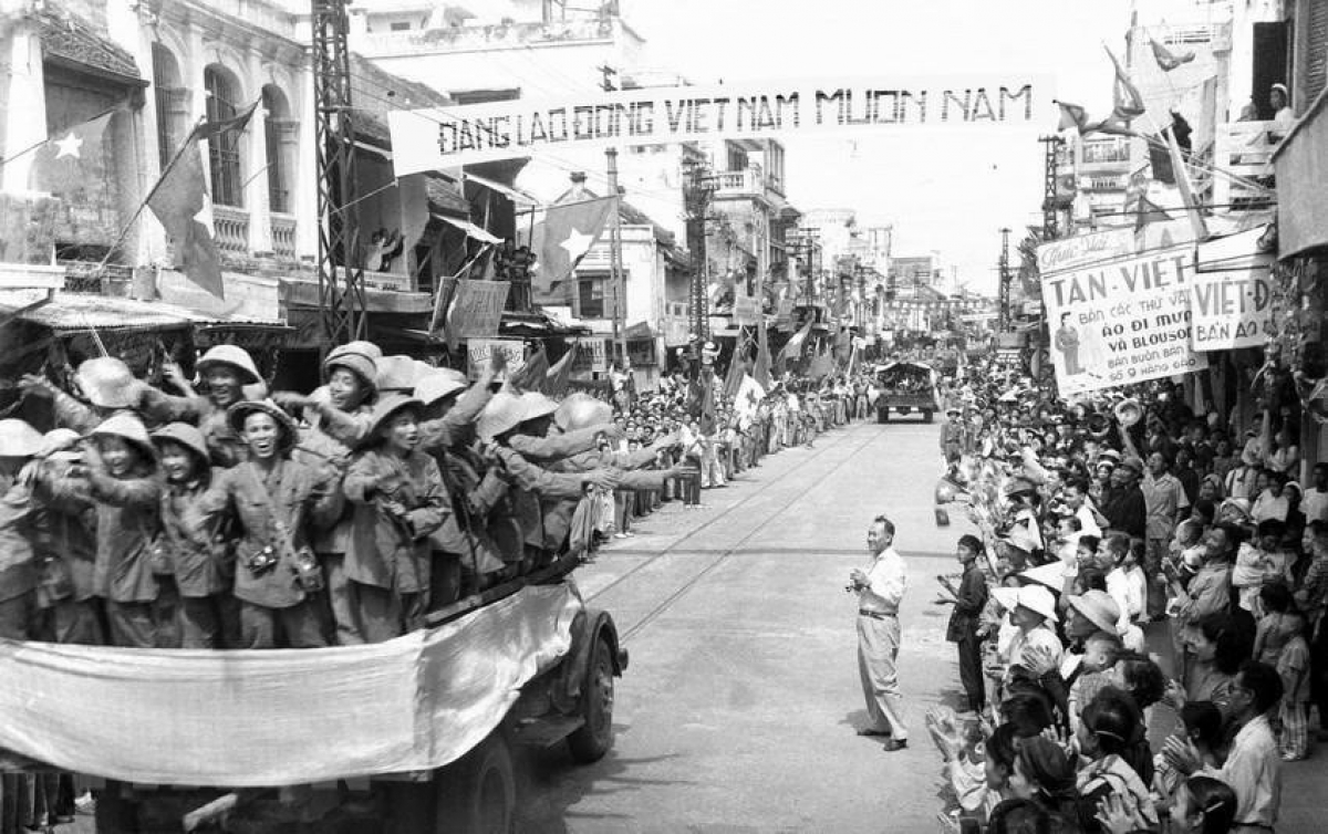 Thousands of Hanoians pour into the streets to greet the arrival of the victorious military forces. Photographed is the scene on Hang Dao street.