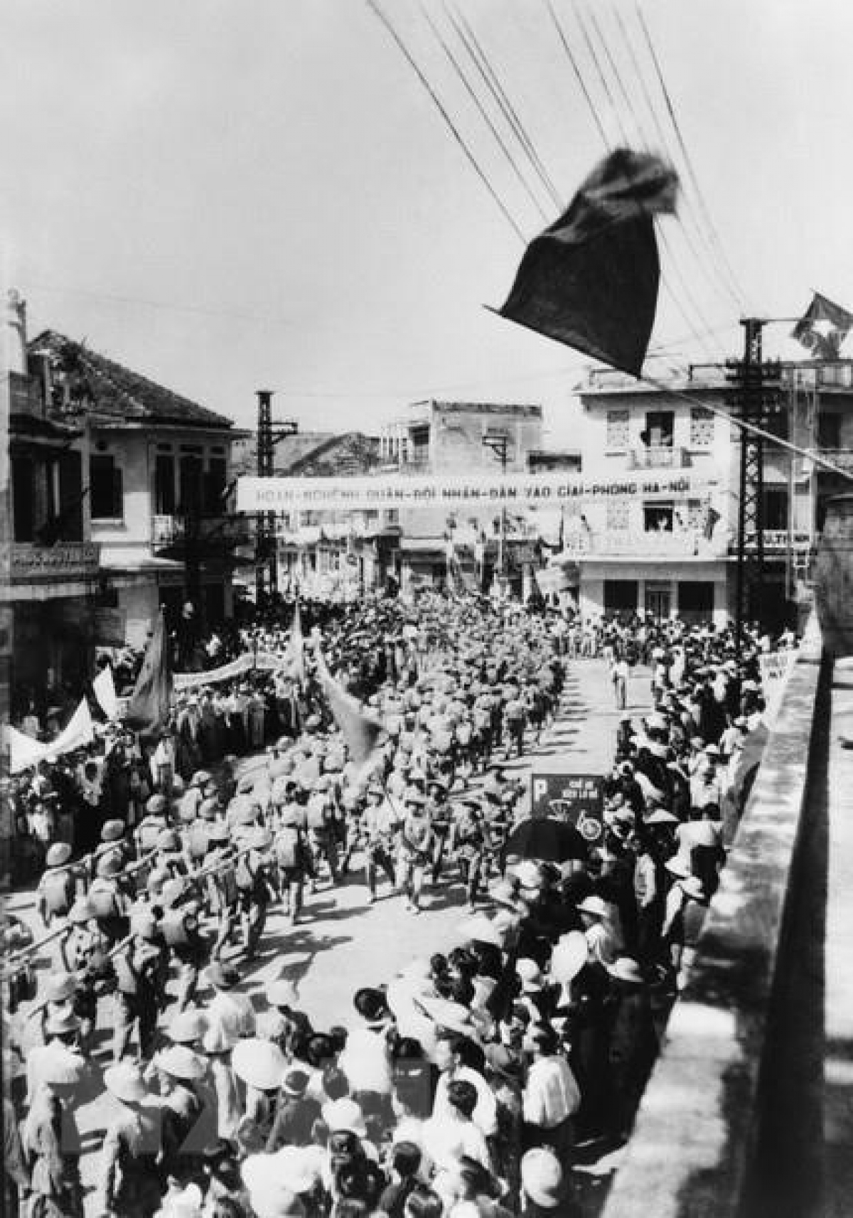Approximately 200,000 residents bearing flags and flowers take to the streets to greet liberation forces. Pictured is the jubilant scenes on Hang Gai street.