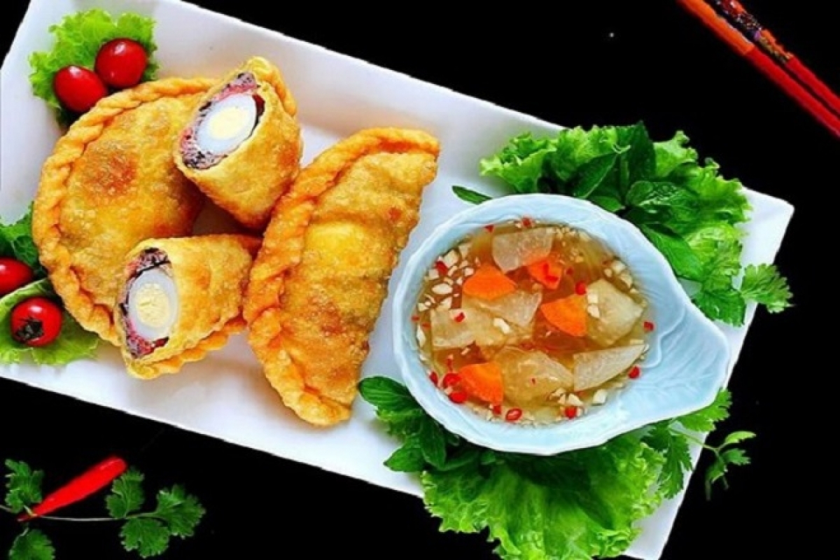 Banh goi, pillow cake, is not baked but deep fried in vegetable oil in order to create a charming yellow pastry skin. Its texture is crispy and smells fragrant. The most important part is making dipping sauce with the exact proportion of garlic, chili, sugar, lime juice, fish sauce, and water.