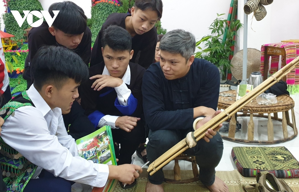 Boys study how to play an ethnic flute.