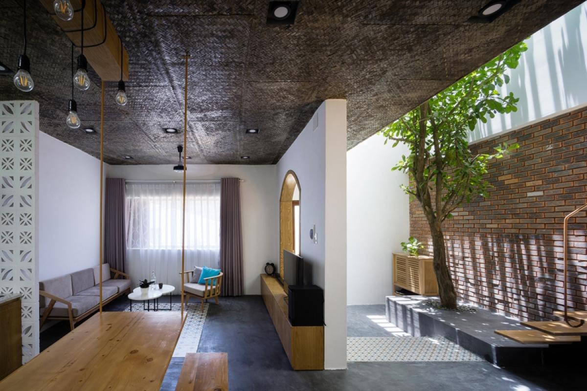 Tầng 1 là không gian liên hoàn kết nối nhau: phòng khách, phòng bếp – ăn và sân trong. Các bức tường và ô cửa được ngăn cách tượng trưng, nhằm đảm bảo khai thác tối đa thông thoáng và ánh sáng tự nhiên; nhờ đó tầm nhìn cũng được mở rộng. Màu sẫm của trần và nền tương phản mạnh với màu của các bức tường trắng, như một nét cá tính của công trình.