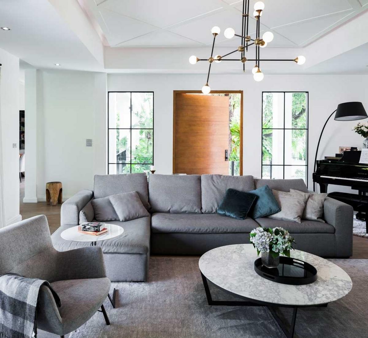 Sofa lớn kèm với tấm thảm cùng tông chiếm phần lớn diện tích phòng khách.
