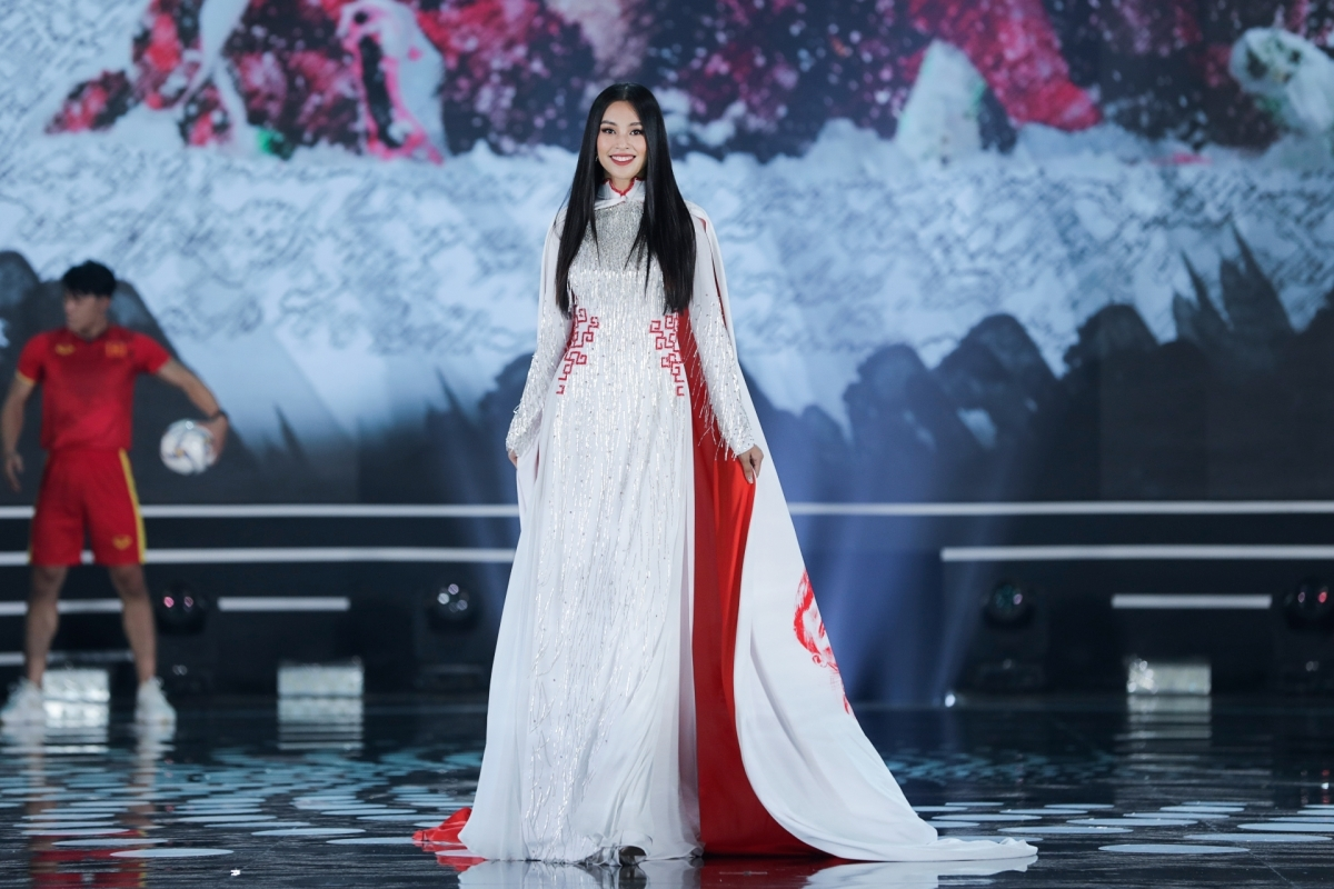 Tieu Vy, Miss Vietnam 2018, shines in an Ao Dai featuring a picture that offers encouragement to the Vietnamese U23 men's national football team.