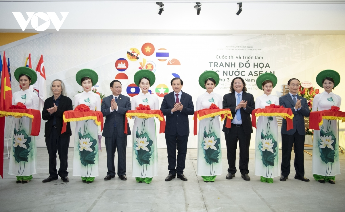 Deputy Minister of Culture, Sports and Tourism Ta Quang Dong (C) joins with other delegates to cut the ribbon to mark the opening of the exhibition on November 6.