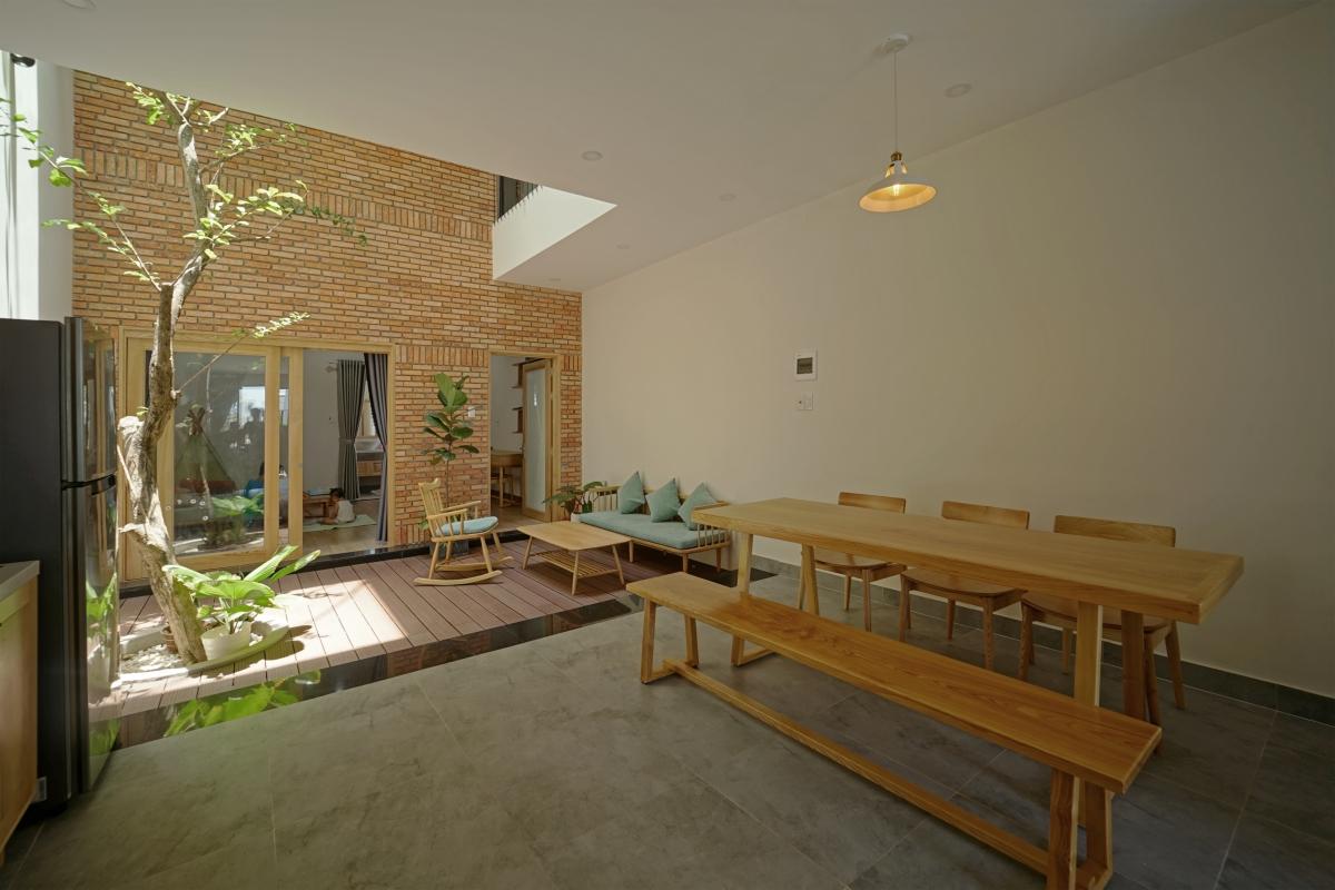 Sàn nhà bê tông xám, nội thất gỗ ấm áp và tường gạch mang lại cảm giác nhẹ nhàng, ấm cúng.