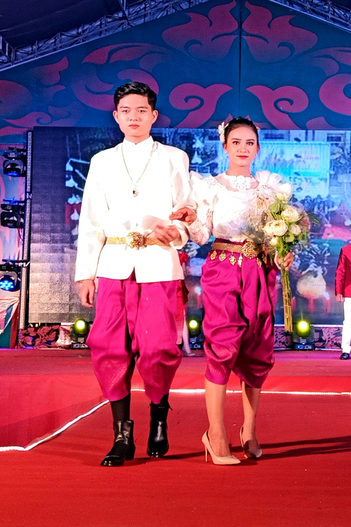 Khmer models don traditional evening outfits on stage at the event.