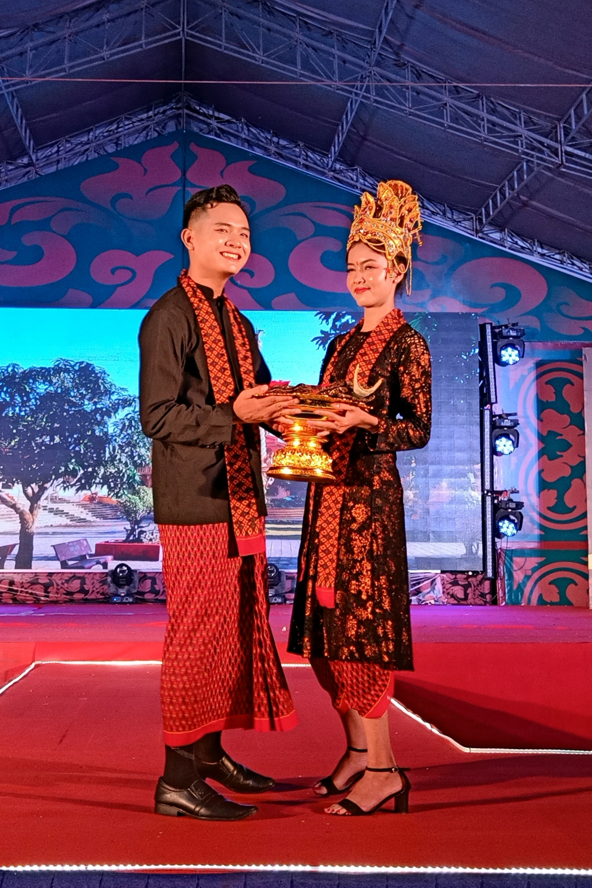 A couple pose on stage as they wear wedding outfits which are typical of the Khmer people.