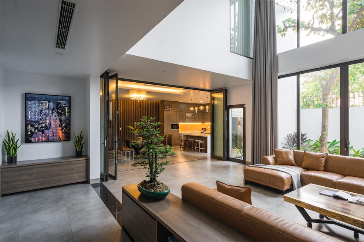 Ngôi nhà dành cho 3 thế hệ - 6 người chung sống. Tầng 1 là một không gian chung mang lại kết nối cho các thành viên trong gia đình. Có thể thấy phòng khách liên thông với phòng ăn, nhưng ở giữa có một vách kính di động có thể đóng lại khi cần sự riêng biệt.