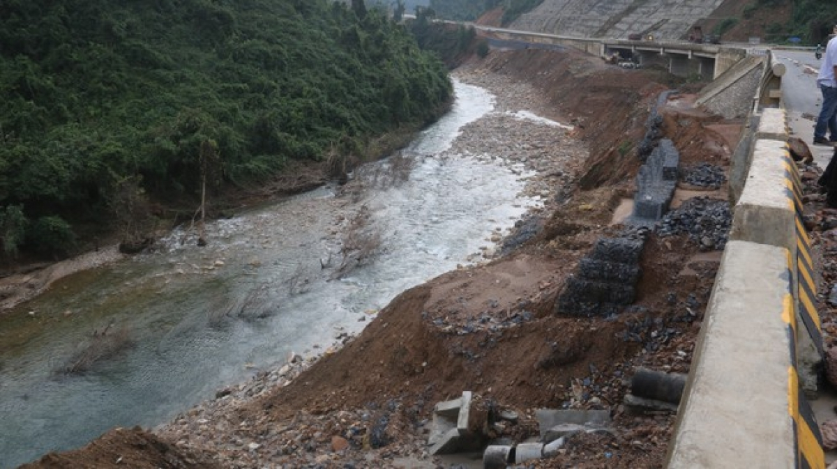 Flood water erodes local roads in central Vietnam, leading to the high risk of landslides.