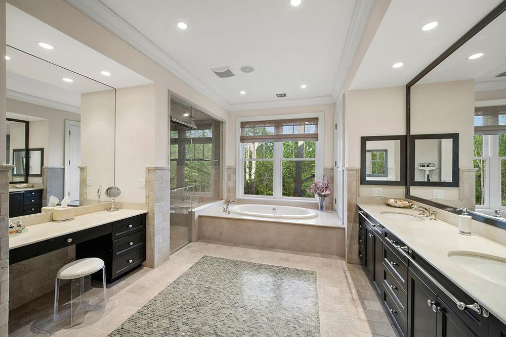 Phòng tắm chính rộng rãi, được lát gạch men màu be, có đầy đủ bồn tắm, vòi sen, và cả bàn trang điểm chuyên dụng.