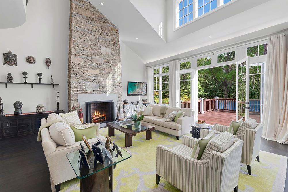 Tiền sảnh dẫn đến phòng khách rộng lớn với điểm nhấn là lò sưởi bằng đá và trần nhà cao chót vót.